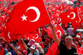 A man waves Turkey's national flag during the Democracy and Martyrs Rally, organized by Turkish President Tayyip Erdogan and supported by ruling AK Party (AKP), oppositions Republican People's Party (CHP) and Nationalist Movement Party (MHP), to prot