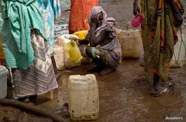 A woman waits in queue to collect water at Yusuf Batil refugee camp, Upper Nile, South Sudan, July 4, 2012.