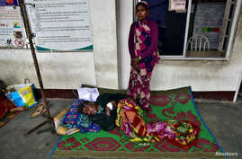 The wife of a tea plantation worker, who consumed bootleg liquor, stands next to her husband as he is being treated in a corridor of a government-run hospital in Golaghat in the northeastern state of Assam, India, Feb. 23, 2019.