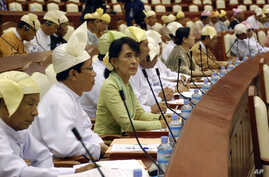 Burma's opposition leader Aung San Suu Kyi, third from left, takes a seat for a regular session of Parliament at Burma's Lower House in Naypyitaw, July 9, 2012.