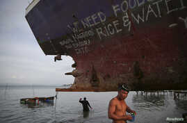 Divers take a part in an effort to recover a ship brought inland by Typhoon Haiyan in Tacloban, in central Leyte province, which Pope Francis will visit this weekend, Jan. 15, 2015.