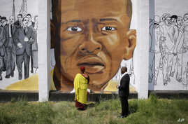 FILE - The Gyalwang Drukpa, bottom center, the Buddhist leader of South Asia, prays in front of a mural depicting Freddie Gray alongside the Rev. Jamal Bryant during a walking tour with other faith and community leaders, Thursday, May 7, 2015.