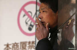 """A man smokes in front of a """"no smoking"""" sign outside a shopping mall in Shanghai, Jan. 10, 2014."""