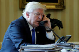 FILE - President Donald Trump conducts a phone call in the Oval Office at the White House in Washington, Jan. 28, 2017.