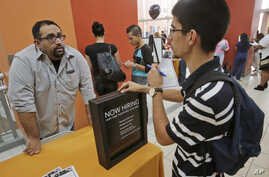 FILE - Job applicant Lazaro Fonte, right, 24, of Miami, talks with Banana Republic assistant manager Edward Ortega, during a job fair at Dolphin Mall in Miami.