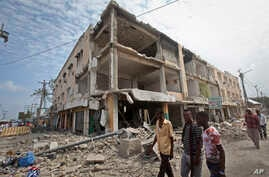 Men walk near destroyed buildings as thousands of Somalis gathered to pray at the site of the country's deadliest attack, Oct. 20, 2017. More than 300 people were killed and nearly 400 wounded in Saturday's truck bombing.