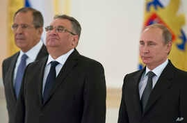 Hungary's Ambassador Janos Balla, center, and Russian President Vladimir Putin pose for a photo after the Hungarian envoy presented his credentials in the Kremlin in Moscow, Russia, Nov. 19, 2014. At left in the background is Russian Foreign Minister