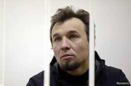 Greenpeace activist Tomasz Dziemianczuk of Poland, one of 30 people arrested over a Greenpeace protest at the Prirazlomnaya oil rig, looks out from a defendants' cage during a court session in St. Petersburg, Russia, Nov. 19, 2013.