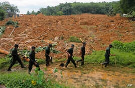 FILE - Sri Lankan army soldiers carry out a search operation in Elangapitiya village in Aranayaka, about 70 kilometers (45 miles) north of Colombo, Sri Lanka, May 19, 2016. Heavy rains pounded the central Sri Lankan region where at least three villag