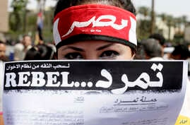 """FILE -  An Egyptian activist covers her face with an application for """"Tamarod"""", Arabic for """"rebel"""", a campaign calling for the ouster of Egyptian President Mohammed Morsi and for early presidential elections, during a protest in Tahrir Square, Cairo."""