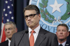 Gov. Rick Perry listens to a reporter's question during a news conference in the governor's press room in Austin, Texas, July 21, 2014.
