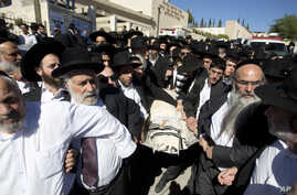 Ultra-Orthodox Jewish men carry the body of 17-year-old student Shalom Baadani during his funeral in Jerusalem, Friday, Nov. 7, 2014.