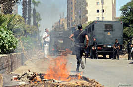Police take positions after a protest was dispersed quickly, leaving fire burning in a main street in Giza, south of Cairo August 14, 2014.