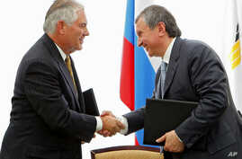 FILE - Igor Sechin, CEO of state-controlled Russian oil company Rosneft (right) and Exxon Mobil Corp. CEO Rex Tillerson shake hands after signing an agreement at the Black Sea port of Tuapse, southern Russia, June 15, 2012.