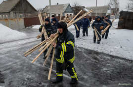Emergencies Ministry members prepare to repair a building which was damaged during fighting between the Ukrainian army and pro-Russian separatists in the government-held industrial town of Avdiyivka, Ukraine, Feb. 6, 2017.