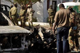 Nigerian bomb experts and military personnel investigate the site of an explosion at a police station in Kano, Nov. 15, 2014.