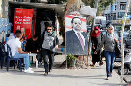 People walk next to a poster depicting Lebanon's Prime Minister Saad al-Hariri, who has resigned from his post, along a street in the mainly Sunni Beirut neighbourhood of Tariq al-Jadideh in Beirut, Lebanon, Nov. 6, 2017.