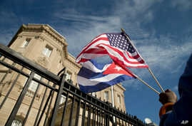 Edwardo Clark, a Cuban-American, holds an American flag and a Cuban flag as he celebrates outside the new Cuban embassy in Washington, July 20, 2015.