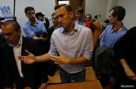 Russian opposition leader Alexei Navalny talks to journalists after he was sentenced by a court to 20 days in jail on charges of repeatedly violating laws governing the organization of public meetings and rallies, during a hearing in Moscow, Russia, ...
