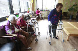 FILE - Kim Gun-ja, 89, right, former comfort woman who was forced to serve for the Japanese troops as a sexual slave during World War II, passes by other comfort woman Yi Ok-seon, 88, left, and Kim Wei-han, 86, at the House of Sharing, a nursing home