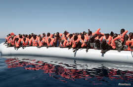 A plastic raft overcrowded with migrants drifts in the central Mediterranean Sea, May 18, 2017. More than 2,000 migrants were rescued overnight Friday.