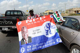 A vendor hawks flags of the ruling National Democratic Congress (NDC) and New Patriotic Party (NPP) in a traffic jam in Kasoa, Central Region on December 1, 2012 ahead of the December 7 presidential elections in Ghana .