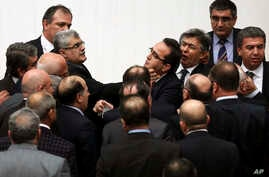 Turkish legislators from Prime Minister Recep Tayyip Erdogan's ruling party and the main opposition Republican People's Party brawl during a tense all-night debate over a controversial law on changes to a council that appoints and overseas judges and