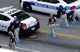 An FBI evidence response team works the crime scene, July 10, 2016, where five Dallas police officers were killed Thursday, in Dallas.