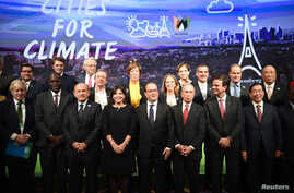 FILE - French President Francois Hollande (C) poses with local representatives including Paris Mayor Anne Hidalgo (4thL), London Mayor Boris Johnson (L), New York Mayor Michael Bloomberg (3rdR), Seoul Mayor Park Won-soon (R), Istanbul Mayor Kadir Top