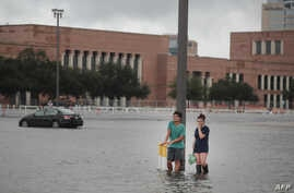 Grant Lu (L) and Naomi Pringle stand in a flooded parking lot on the campus of Rice University afer it was inundated with water from Hurricane Harvey on Aug. 27, 2017 in Houston, Texas.
