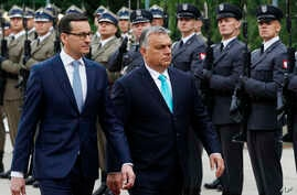 Hungary's Prime Minister Viktor Orban is greeted by his Polish counterpart Mateusz Morawiecki at the start of his one-day visit, at the Lazienki Palace in Warsaw, Poland, May 14, 2018.
