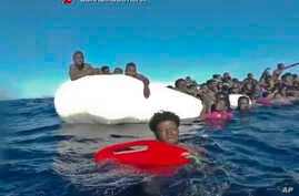 This frame of a video taken by the Italian Coast Guard on Jan. 6, 2018, in the Mediterranean Sea off Libya, shows migrants being rescued from dinghies as they try to cross to Italy.