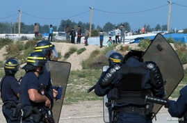 "French riot police stand guard at the entrance to ""the Jungle"" as dozens of migrants try to storm trucks that are heading toward the ferry terminal in Calais, France, Sept. 21, 2016."