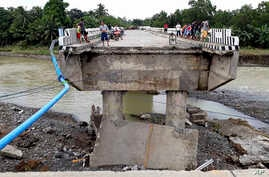 People gather on a bridge that was damaged by the flooding brought about by tropical storm Tembin, Dec. 24, 2017, in Zamboanga Del Sur in southern Philippines.