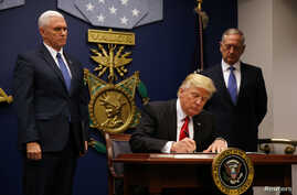 FILE - President Donald Trump signs the initial executive order for a U.S. travel ban, Jan. 27, 2017, at the Pentagon.