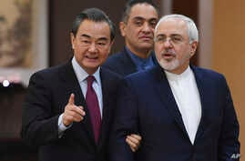 "Iranian Foreign Minister Mohammad Javad Zarif (R) arrives with Chinese Foreign Minister Wang Yi for a joint press conference in Beijing, China, Dec. 5, 2016. Zarif said that nations party to the Iran nuclear deal ""have the obligation to fully impleme"
