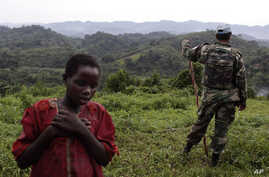 FILE - A Congolese girl walks past a Uruguayan United Nations peacekeeper.