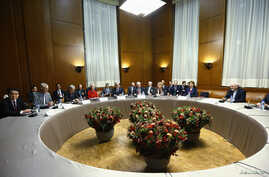 European Union foreign policy chief Catherine Ashton (2nd R) speaks with Iranian Foreign Minister Mohammad Javad Zarif (R) before the start of two days of closed-door nuclear talks at the United Nations European headquarters in Geneva, Switzerland, N