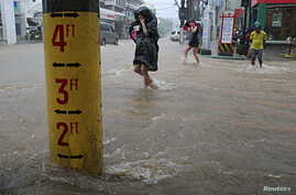 FILE - A flood warning gauge is seen along a flooded road after tropical storm Linfa hit the Philippines, July 6, 2015.