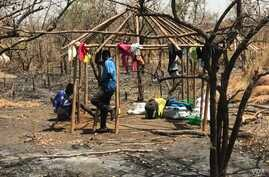 Two South Sudanese brothers build a hut at the Imvempi settlement in Arua district, Uganda, Jan. 30, 2018. (H. Athumani/VOA)