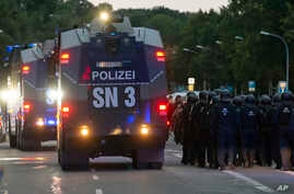 "A police water cannons passes by a far-right protest in front of a Karl Marx monument in Chemnitz, Germany, Monday, Aug. 27, 2018 after a man has died and two others were injured in an altercation between several people of ""various nationalities"" in"