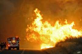 Firefighters from the Lompoc City Fire Department take shelter behind their engine on June 16, 2016, as wind driven flames advance from the Sherpa Fire.