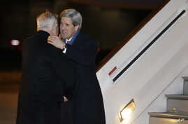 U.S. Secretary of State John Kerry, right, is greeted by U.S. Ambassador Louis Susman upon his arrival in Britain marking the start of his first official trip overseas, at Stansted Airport east of London, Feb. 24, 2013.
