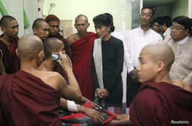 Burmese pro-democracy leader Aung San Suu Kyi visits Buddhist monks, wounded in a recent police crackdown on protesters against a copper mine project, Nov. 29, 2012.