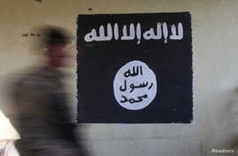 FILE - A soldier walks past a black flag commonly used by Islamic State militants.