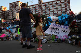 People gather at a makeshift memorial outside of the Dallas police department headquarters on July 12, 2016 in Dallas, Texas.