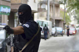 Police in Kosovo arrested 15 people Wednesday in the second major operation in weeks to stem the flow of young ethnic Albanians joining Islamist fighters in Iraq and Syria, a police source said. A masked police officer stands guard in front of a cour