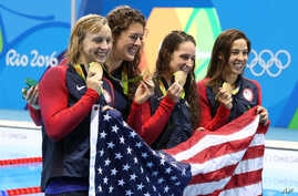 The United States team, Katie Ledecky, Allison Schmitt, Leah Smith and Maya DiRado, from left, hold up their gold medals after winning the women's 4x200-meter freestyle relay during the swimming competitions at the 2016 Summer Olympics, Thursday, Aug
