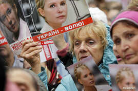 Supporters of Ukraine's jailed former Prime Minister Yulia Tymoshenko hold up posters of Tymoshenko, during a rally near the high court building in Kiev, August 29, 2012.