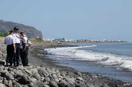 Police officers inspect metallic debris found on a beach in Saint-Denis on the French Reunion Island in the Indian Ocean on August 2, 2015, close to where a Boeing 777 wing part believed to belong to missing flight MH370 washed up last week.